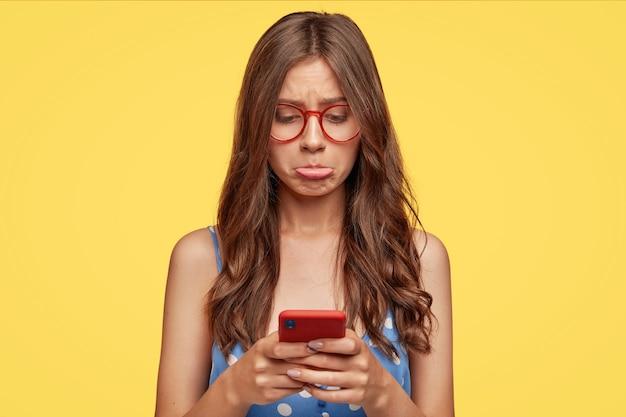 Mulher caucasiana descontente tem expressão ofensiva, franze os lábios inferiores em desgosto, usa um telefone celular moderno