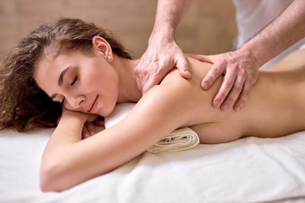 Mulher caucasiana, desfrutando de uma massagem relaxante de corpo inteiro nos antebraços e cúbitos no centro de spa de cosmetologia