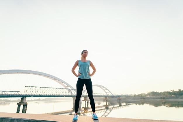 Mulher caucasiana desportiva em pé no kay com as mãos nos quadris de manhã. na ponte de fundo. comprimento total.