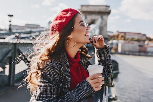 Mulher caucasiana despreocupada com chapéu vermelho, apreciando a vista da cidade em um dia quente de vento