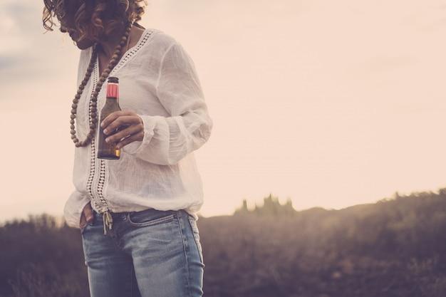 Mulher caucasiana despreocupada com colar de miçangas de madeira e garrafa de cerveja gelada na mão, explorando e desfrutando ao ar livre. mulher hippie se divertindo bebendo cerveja durante as férias