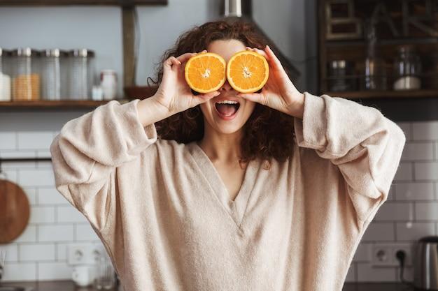 Mulher caucasiana divertida sorrindo e segurando duas partes de laranja enquanto toma café da manhã no interior da cozinha em casa