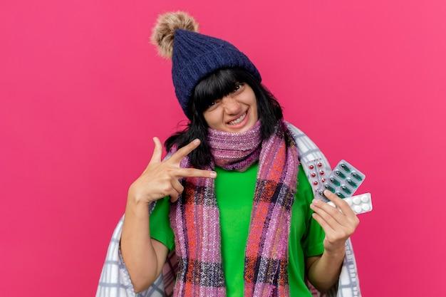 Mulher caucasiana doente e sorridente usando chapéu de inverno e lenço embrulhado em uma manta segurando pacotes de comprimidos médicos, mostrando gesto de três dedos isolado