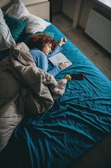 Mulher caucasiana dormindo com cabelos cacheados se sentindo cansada depois de fazer a lição de casa segurando uma caneta e descansando perto de um livro e um celular