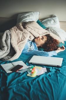 Mulher caucasiana dormindo está descansando depois de fazer a lição de casa no laptop na cama coberta com uma colcha e de pijama