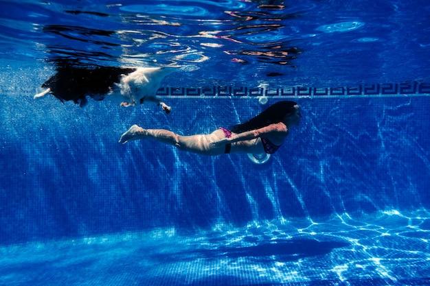 Mulher caucasiana e cão border collie nadando na piscina. visão subaquática. horário de verão e conceito de férias