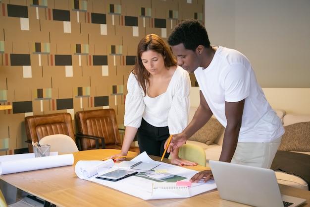 Mulher caucasiana e cara afro-americana criando um novo design e escrevendo no papel