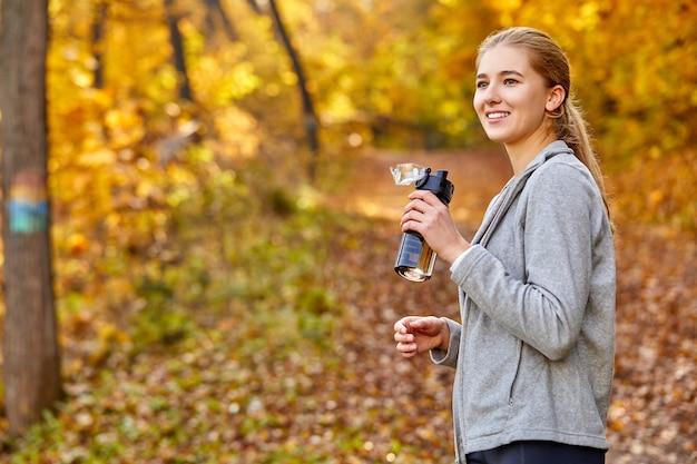 Mulher caucasiana e desportiva com garrafa de água ao ar livre