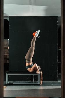 Mulher caucasiana e desportiva em sportswear fazendo pose de sarvangasana no banco.