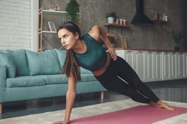 Mulher caucasiana e esportiva fazendo uma prancha lateral durante uma sessão de ginástica em casa no chão