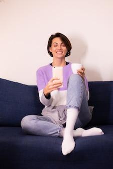 Mulher caucasiana e fofa blogueira em casa usando um agasalho de suéter roxo e tirar uma selfie no espelho do celular
