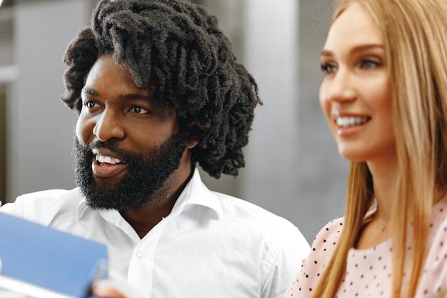 Mulher caucasiana e homem afro passando passaportes para a recepção do hotel fecham