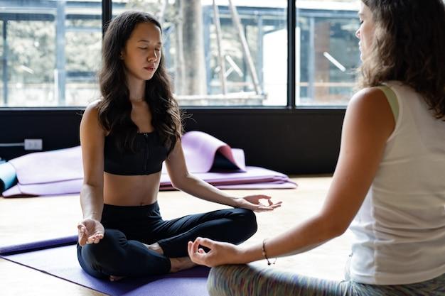 Mulher caucasiana e mulher asiática amigo sentado em meditação, fazendo ioga no tapete de ioga na sala de exercícios no ginásio com espaço de cópia. mulher com exercícios fazendo ioga juntos no interior com o conceito de ioga.