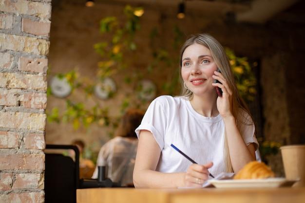 Mulher caucasiana e sorridente em uma camiseta branca olha para o lado enquanto fala ao telefone e escreve no papel com um croissant e café em um café na mesa