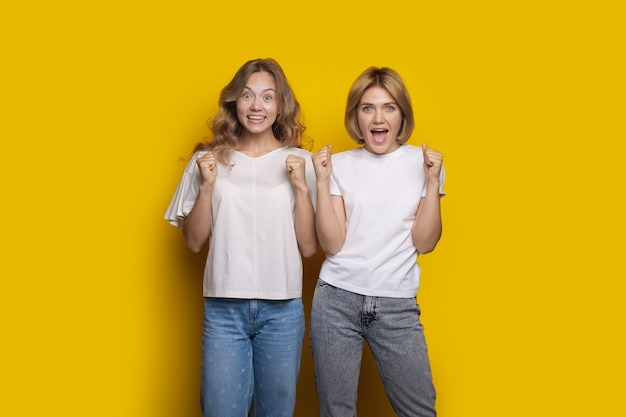 Mulher caucasiana é surpreendida por algo posando em uma parede amarela e gesticulando com os punhos