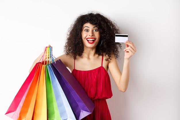 Mulher caucasiana elegante com cabelo encaracolado e vestido vermelho, mostrando sacolas de compras e seu cartão de crédito de plástico, sorrindo divertido, em pé sobre um fundo branco.