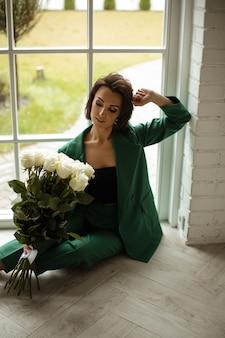 Mulher caucasiana elegante com cabelo escuro em um terno verde posa para a câmera e tem um grande buquê de flores brancas na mão