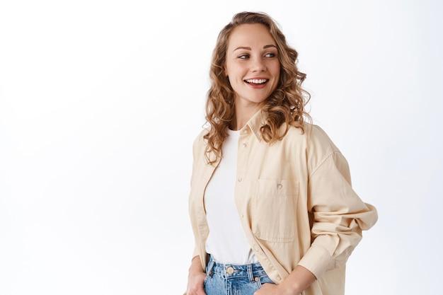 Mulher caucasiana elegante com cabelo loiro encaracolado, olhando de lado para o texto promocional e sorrindo satisfeita, em pé contra uma parede branca
