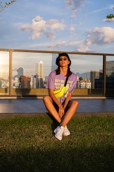 Mulher caucasiana elegante no panamá da moda e bolsa de néon na cintura no telhado em bangkok com vista
