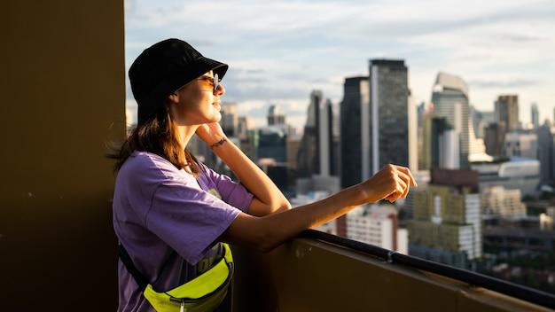 Mulher caucasiana elegante no panamá da moda e bolsa de neon na cintura no telhado em bangkok