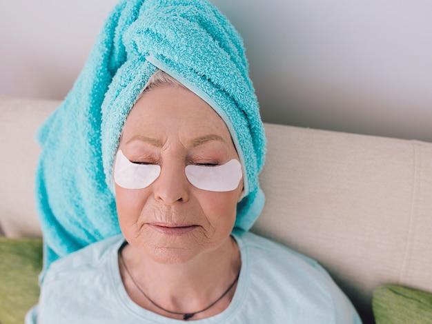 Mulher caucasiana elegante sênior deitada em uma carruagem com uma toalha azul tinha tapa-olhos de colágeno