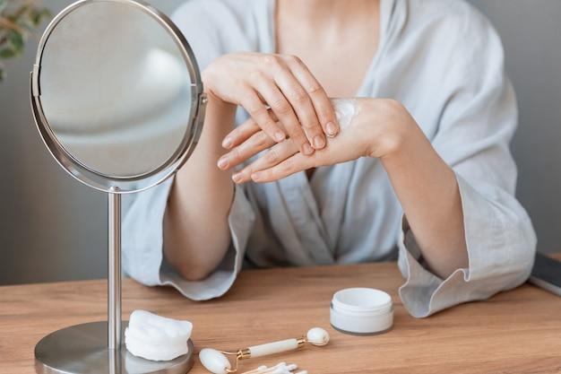 Mulher caucasiana em casa ou no spa aplica creme para as mãos ou bálsamo corporal