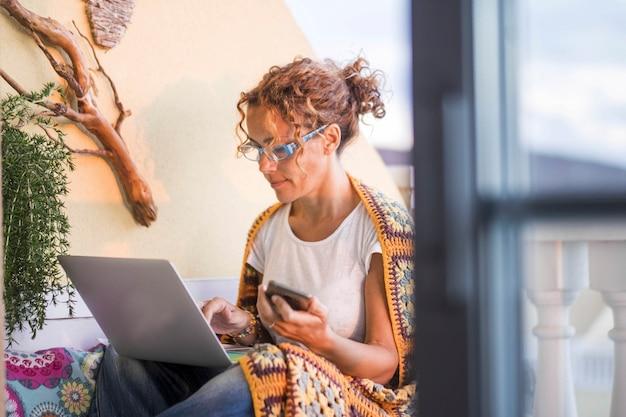 Mulher caucasiana em casa usa laptop pessoal ao ar livre no terraço