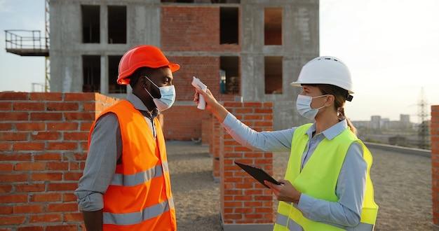 Mulher caucasiana em casque e máscara médica, medindo e verificando a temperatura em trabalhadores mistos de homens do lado da construção. construtores e engenheiros de várias etnias chegando na construção da pandemia