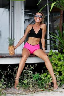 Mulher caucasiana em forma de short rosa preto segurando abacaxi do lado de fora de villa tropical