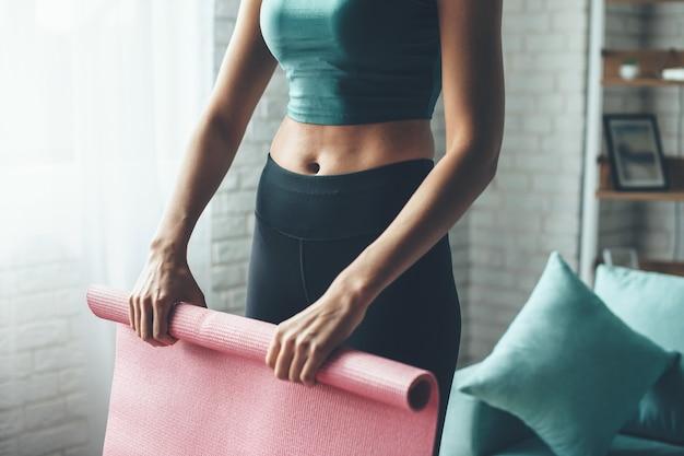 Mulher caucasiana em forma usando roupas esportivas enquanto pega o tapete de ioga