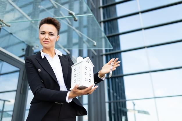Mulher caucasiana em roupas de escritório mantém uma pequena casa branca e espera colega perto do prédio de escritórios
