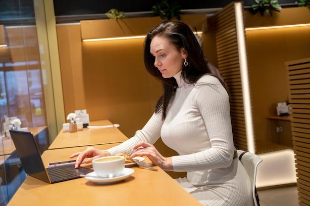 Mulher caucasiana em um café trabalhando em um laptop e bebendo café