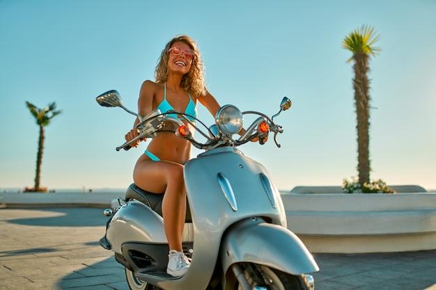 Mulher caucasiana em um maiô biquíni e óculos em uma scooter de bicicleta perto da praia em um dia ensolarado.