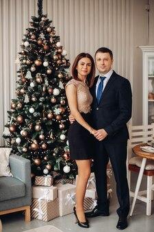 Mulher caucasiana em vestido curto posa para a câmera com o namorado perto da árvore de natal