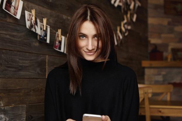 Mulher caucasiana encantadora com cabelo castanho chocolate e sorriso misterioso
