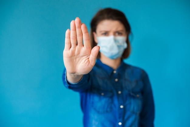 Mulher caucasiana encantadora com camisa jeans azul e máscara médica gesticulando para a placa de pare na parede