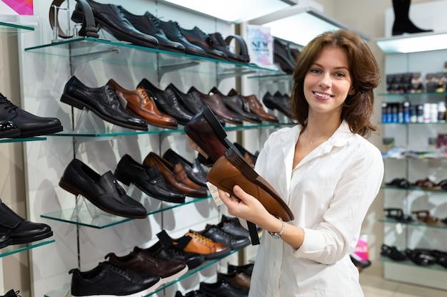 Mulher caucasiana escolhe entre dois pares de sapatos masculinos em uma loja de sapatos