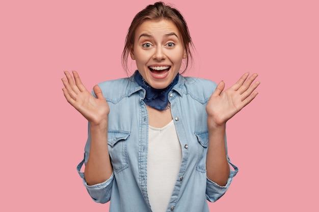Mulher caucasiana espantada e alegre espalha as palmas das mãos, animada com as boas notícias e tem um sorriso cheio de dentes