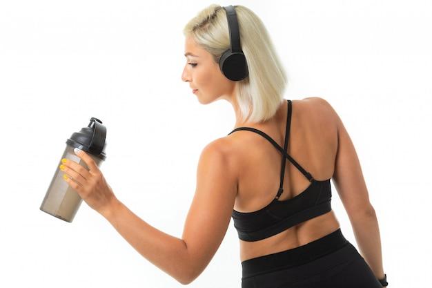 Mulher caucasiana esporte com cabelo loiro ouvir música com fones de ouvido grandes e bebe água com garrafa de esporte
