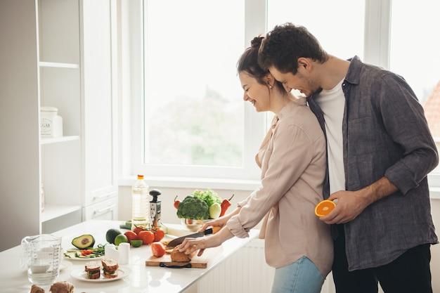 Mulher caucasiana está fatiando pão para fazer sanduíches enquanto seu amante a abraça e sorri