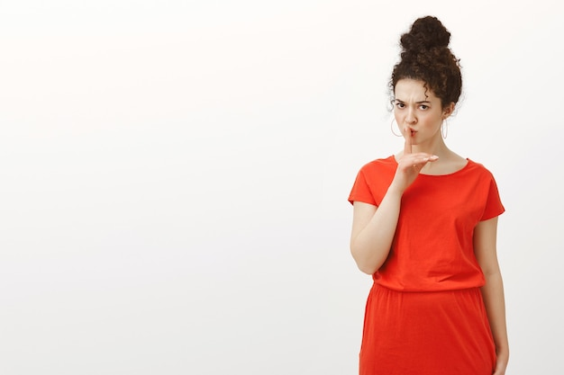 Mulher caucasiana estrita e bonita com cabelo encaracolado em um vestido vermelho casual, dizendo shh, fazendo um gesto de aviso de silêncio com o dedo indicador sobre a boca, franzindo a testa