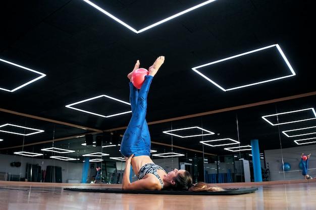Mulher caucasiana, exercitando exercícios de bola de fitness de pilates em um ginásio moderno.