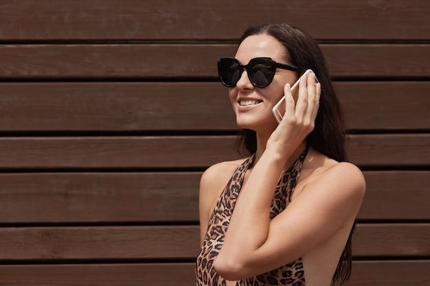 Mulher caucasiana fala telefone celular perto de uma parede de madeira marrom, vestindo um elegante maiô e óculos escuros.