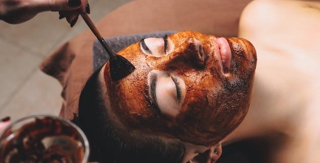 Mulher caucasiana fazendo tratamento facial com máscara de cacau aplicada no salão do spa
