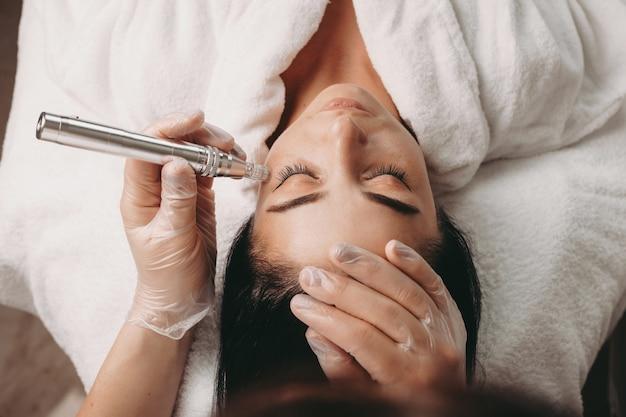 Mulher caucasiana fazendo um procedimento anti-envelhecimento com aparelhos modernos durante uma sessão de spa