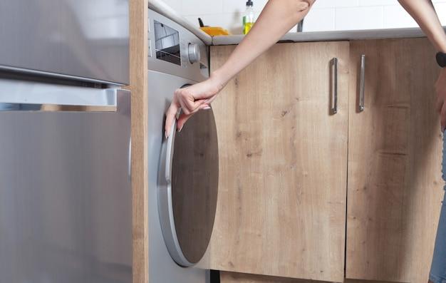 Mulher caucasiana, feche a porta da máquina de lavar.