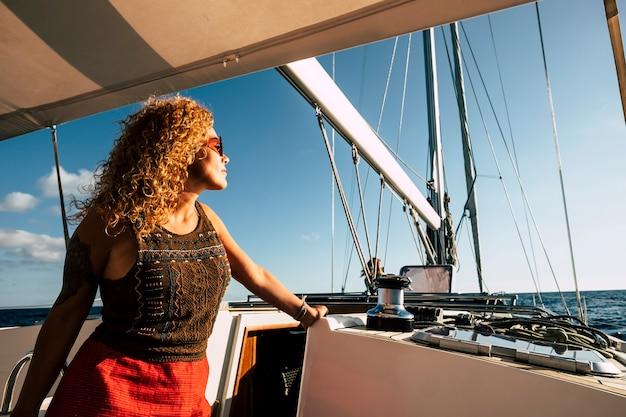 Mulher caucasiana feliz aproveita o transporte de turismo em um barco à vela