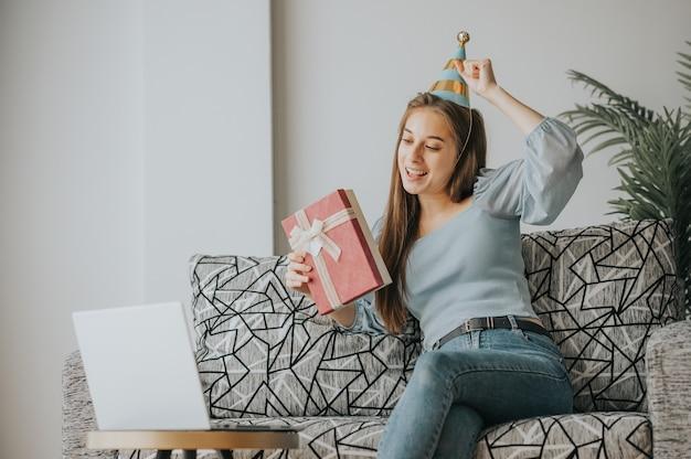 Mulher caucasiana feliz comemora durante o ano novo ou aniversário por meio de videochamada no laptop em casa segurando uma caixa de presente presente