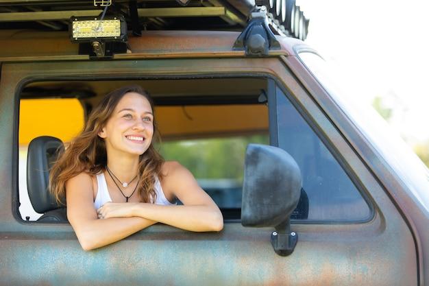 Mulher caucasiana feliz do retrato dirige uma velha van vintage campista na estrada.