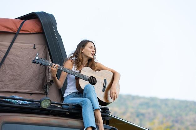 Mulher caucasiana feliz gosta de tocar violão e cantar música, belas férias no carro com a barraca no telhado. caravana em belas férias